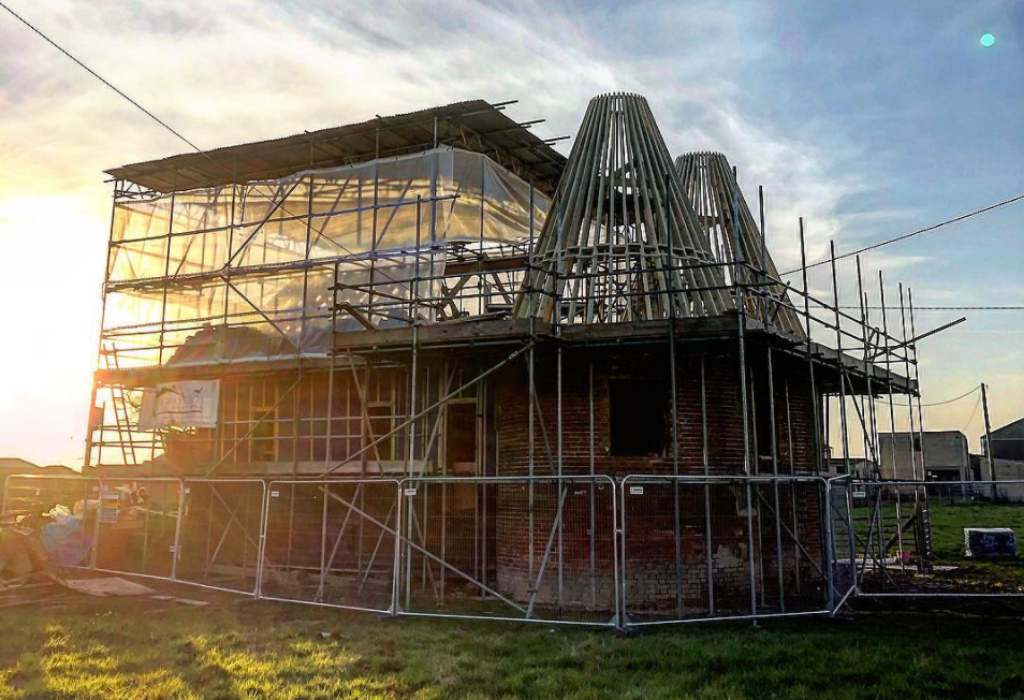 Oast house conversion with scaffolding around it